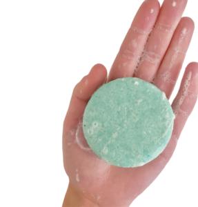 Une barre de shampoing bleu dans la main d'une personne