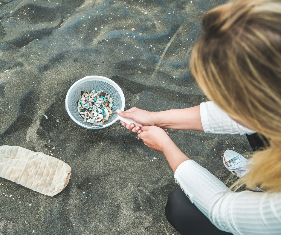 Femme ramassant des morceaux de microplastiques mélangé au sable d'une plage